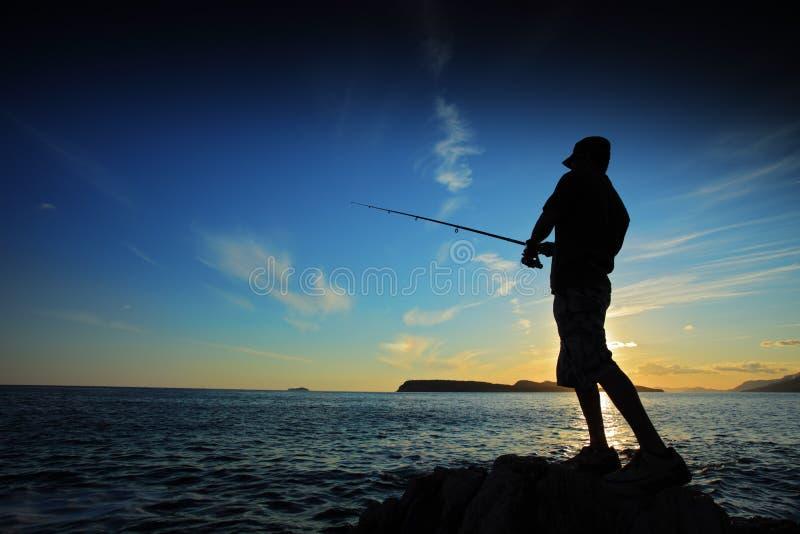 Mens die op zonsondergang vist stock fotografie