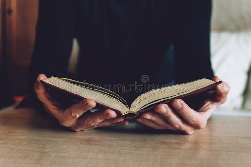 Mens die Open boek in handen houden De mannelijke handen houden een hardcoverboek Onderwijs, literatuur die, kennis, concept leze stock foto