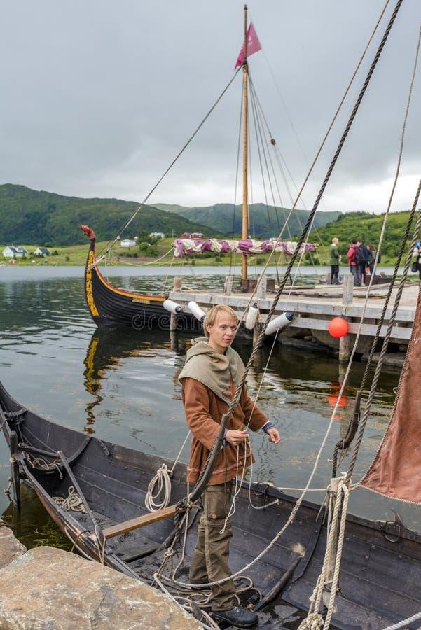 Mens die Opnieuw opgebouwde Viking-boot in de grens van het zoute meer van Innerpollen in Vestvagoy-eiland van Lofoten-archipel v royalty-vrije stock foto