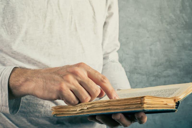 Mens die oud boek met gescheurde pagina's lezen stock foto's