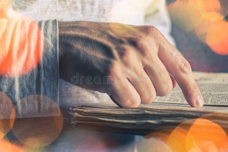 Mens die oud boek met gescheurde pagina's lezen stock afbeelding