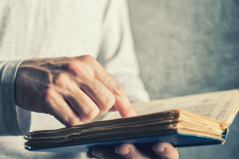 Mens die oud boek met gescheurde pagina's lezen stock fotografie