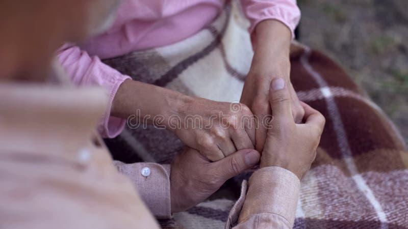 Mens die oude vrouwelijke handen, familieliefde en zorg, oud paar in verpleeghuis houden royalty-vrije stock afbeeldingen