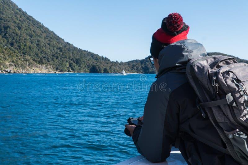 Mens die over de kant van een boot in Nieuw Zeeland met zijn camera kijken stock afbeeldingen