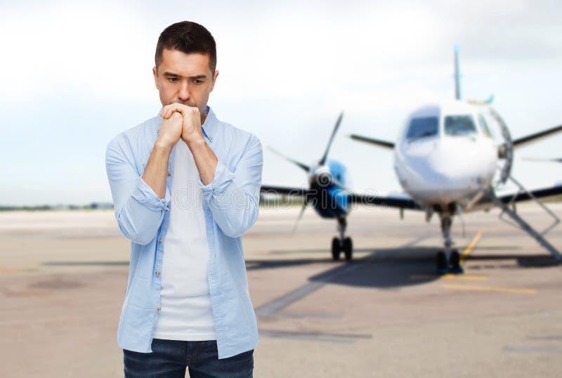 Mens die over vliegtuig op baanachtergrond denken royalty-vrije stock afbeelding