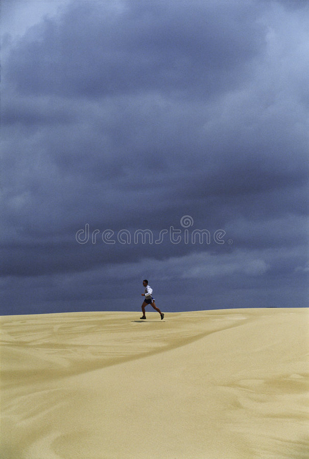 Mens die over zandvlakten loopt royalty-vrije stock afbeelding