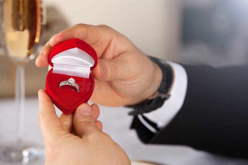 Mens die overeenkomstendoos met ring geven royalty-vrije stock afbeeldingen