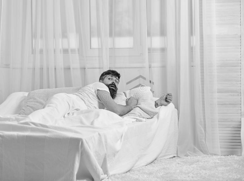 Mens die in overhemd op bed wakker, wit gordijn leggen op achtergrond Het kielzog omhoog en verslaapt zich concept Kerel op verra royalty-vrije stock afbeeldingen