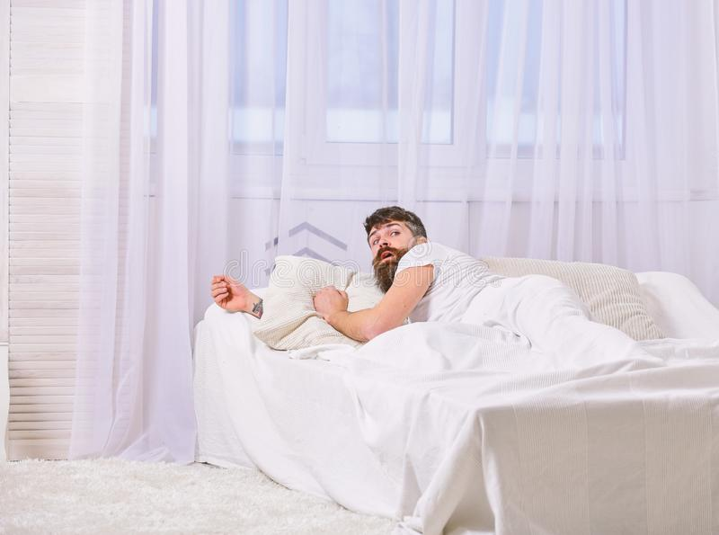 Mens die in overhemd op bed wakker, wit gordijn leggen op achtergrond Het kielzog omhoog en verslaapt zich concept Kerel op verra stock afbeeldingen