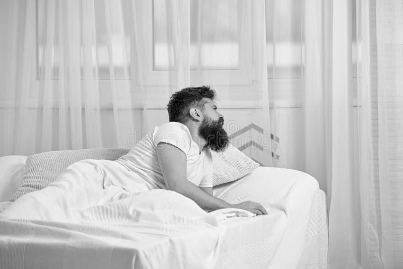 Mens die in overhemd op bed wakker, wit gordijn leggen op achtergrond Katerconcept Kerel bij het teleurgestelde pijnlijke gezicht stock fotografie