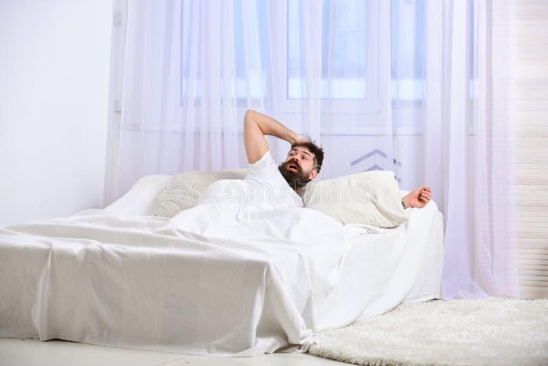 Mens die in overhemd op bed wakker, wit gordijn leggen op achtergrond Kerel op geschokte gezichtsontwaken in ochtend Macho met stock afbeelding