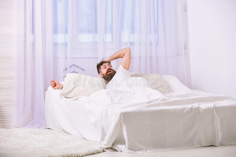 Mens die in overhemd op bed wakker, wit gordijn leggen op achtergrond Kerel op geschokte gezichtsontwaken in ochtend Macho met royalty-vrije stock fotografie
