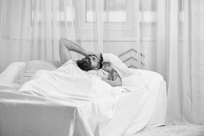 Mens die in overhemd op bed wakker, wit gordijn leggen op achtergrond Kerel op teleurgestelde pijnlijke gezichtsontwaken in ochte stock afbeelding
