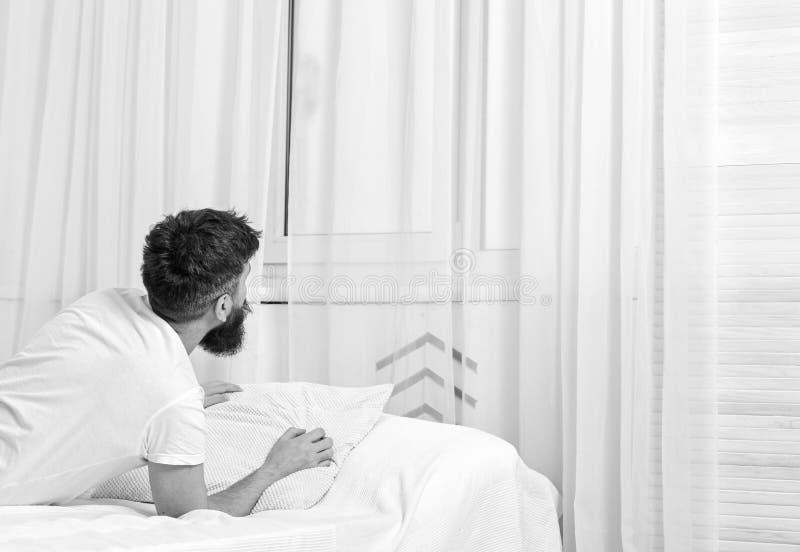 Mens die in overhemd op bed wakker, wit gordijn leggen op achtergrond Kielzog omhoog en ochtendconcept Macho met baard en stock afbeelding