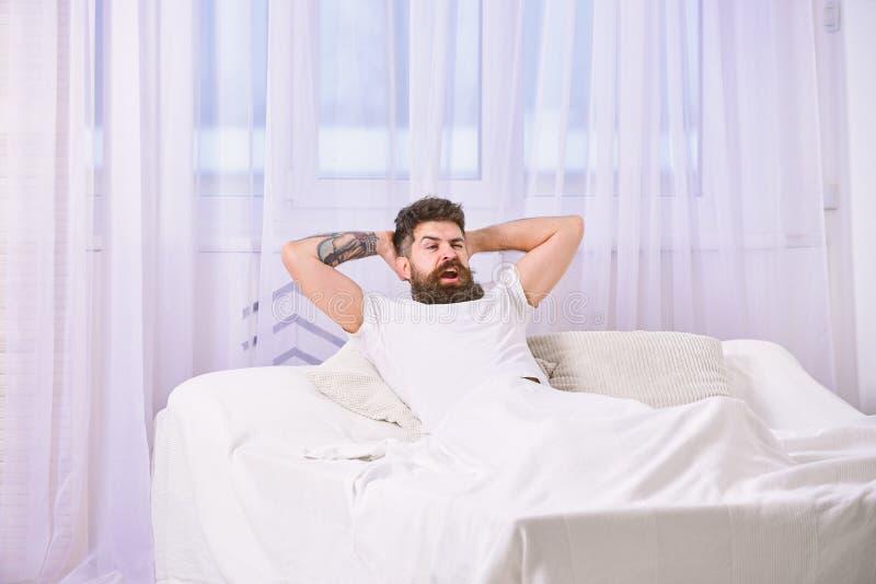 Mens die in overhemd op bed, witte gordijnen op achtergrond leggen Kerel op tevreden gezichtshoogtepunt van energie in ochtend Ho stock foto's
