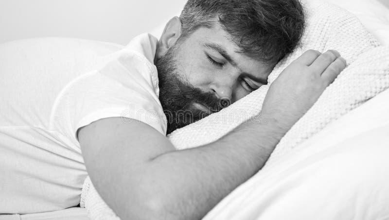 Mens die in overhemd op bed, witte muur op achtergrond leggen Macho met baard en snorslaap, die hebbend dutje, rust ontspannen stock fotografie