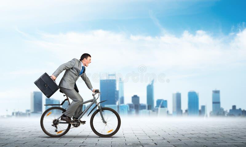 Mens die pak berijdende fiets dragen openlucht stock foto