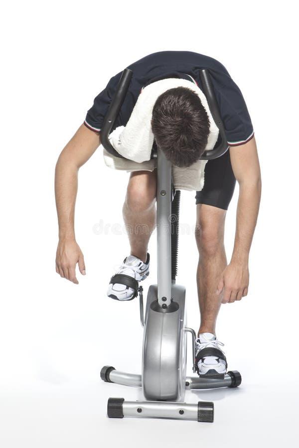 Mens die pedaal stationaire fietsen stock foto's