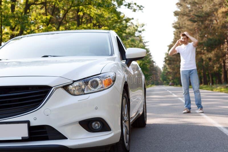 Mens die per mobiele telefoon dichtbij auto spreken royalty-vrije stock foto