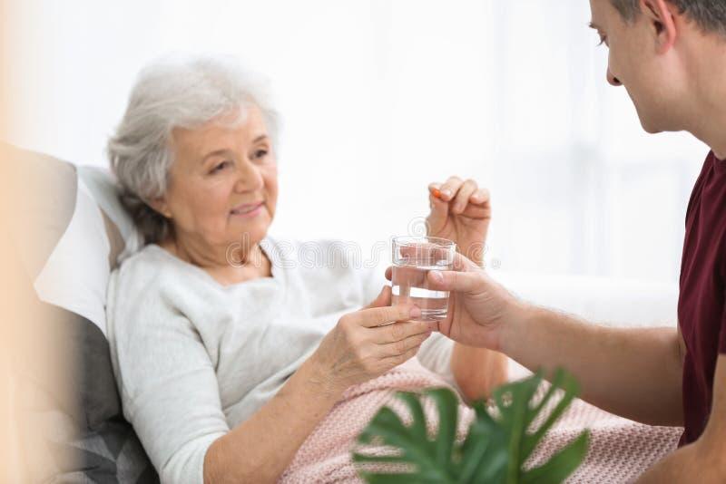 Mens die pil geven aan bejaarde, binnen stock afbeeldingen