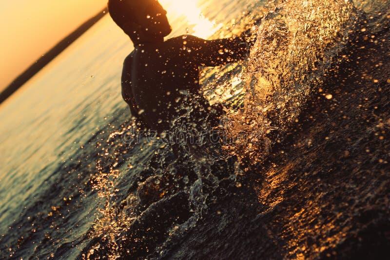 Mens die pret in het water hebben bij zonsondergang royalty-vrije stock afbeelding