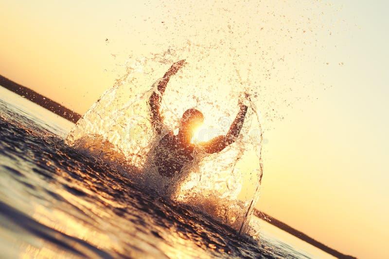 Mens die pret in het water hebben bij zonsondergang Silhouet bij zonsondergang stock fotografie