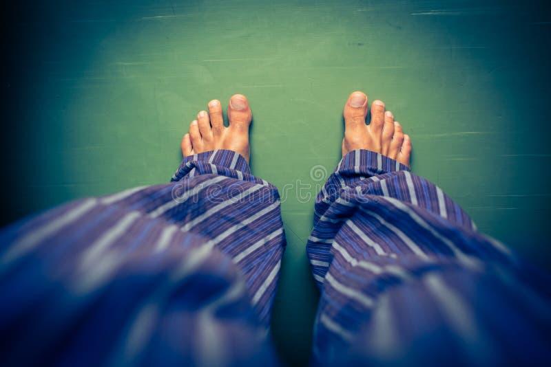 Mens die in pyjama neer op zijn naakte voeten kijken stock foto