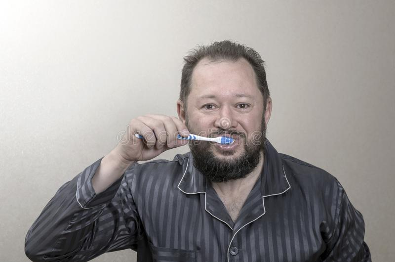 Mens die in pyjama's zijn tanden met een tandenborstel borstelen royalty-vrije stock foto's