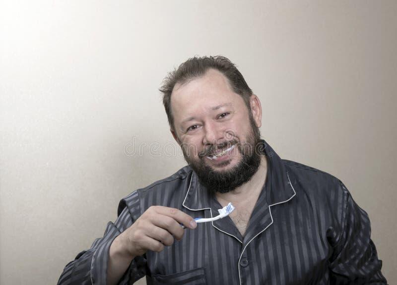 Mens die in pyjama's zijn tanden met een tandenborstel borstelen stock fotografie
