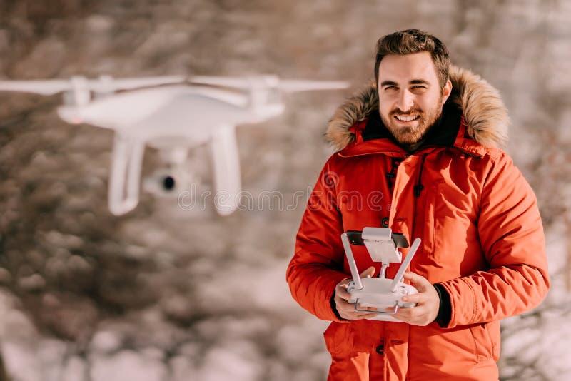 Mens die quadcopter, moderne technologiehommel met afstandsbediening tijdens koude de wintertijd werken stock foto's