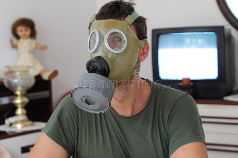 Mens die retro gasmasker thuis dragen stock afbeelding