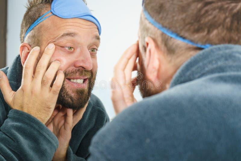 Mens die rimpels op zijn gezicht bekijken stock foto's