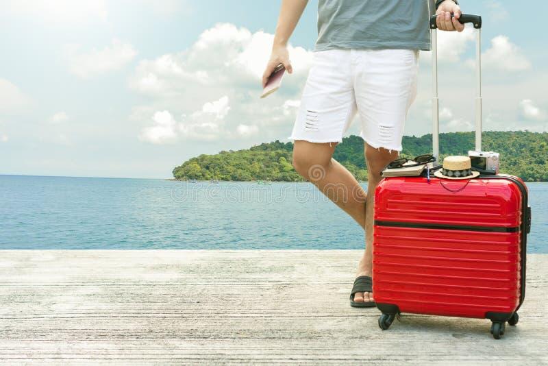 Mens die Rode bagage met paspoort op vage stadsachtergrond houden voor de vrijheid van de activiteitenlevensstijl in openlucht of stock fotografie
