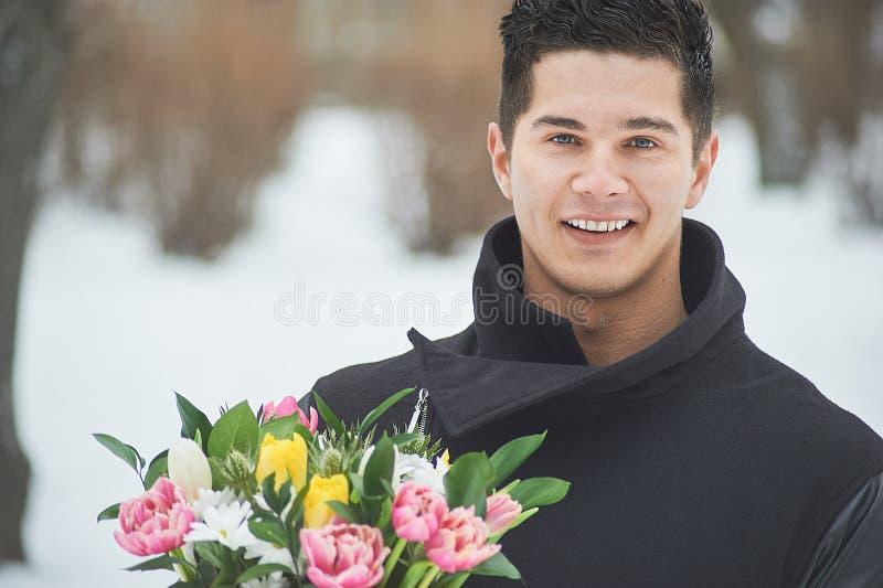 Mens die rode giftdoos met mooi boeket van bloeiende roze, gele en witte tulpen en witte chrysanten met groene leav houden stock afbeelding