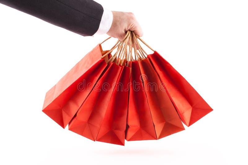 Mens die rode het winkelen zakken houden royalty-vrije stock afbeeldingen