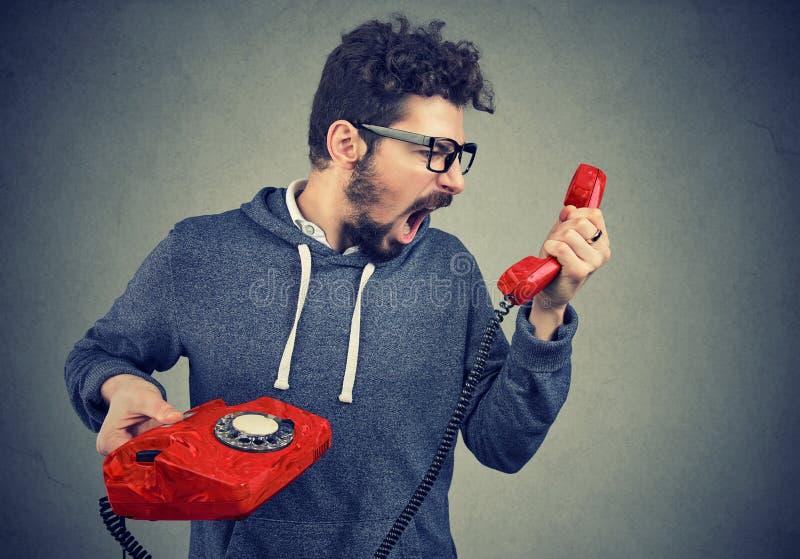 Mens die rode telefoonontvanger houden en in woede schreeuwen royalty-vrije stock foto's