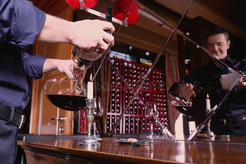 Mens die rode wijn gieten in glas stock foto