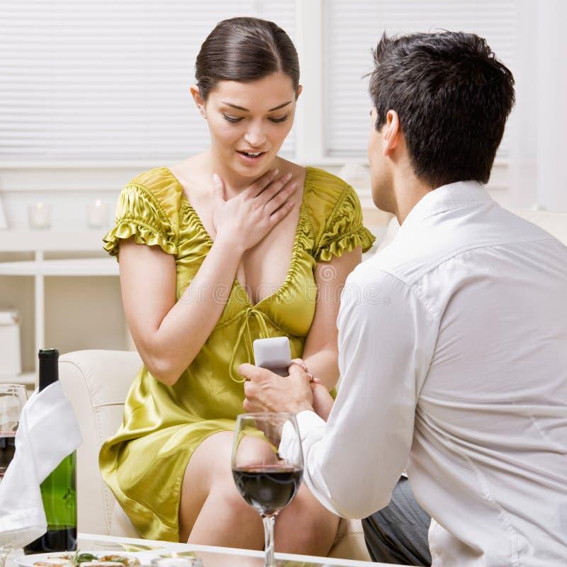 Mens die romantically aan verrast meisje voorstelt royalty-vrije stock afbeelding
