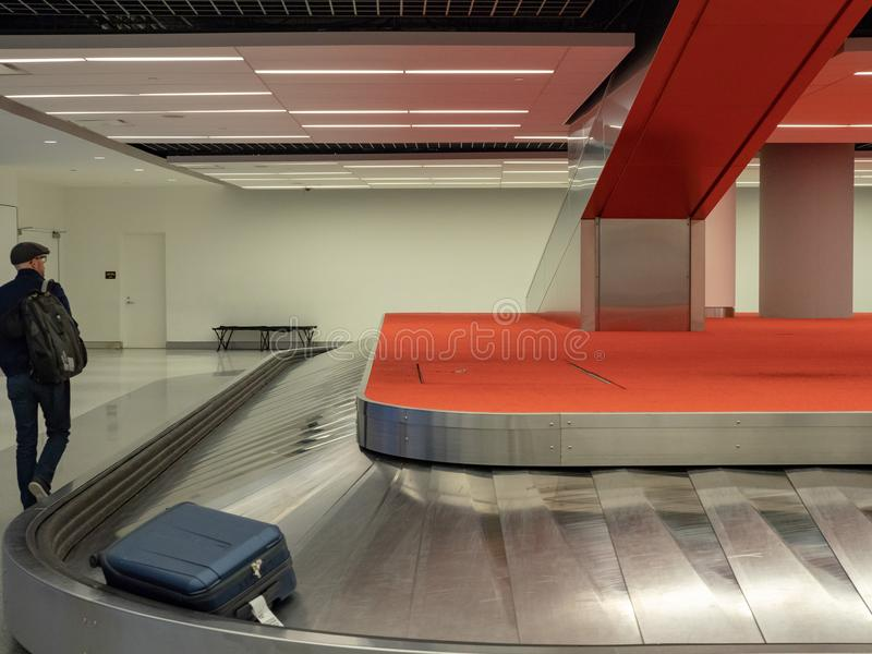 Mens die rond bagagebandcarrousel lopen in luchthaven stock foto