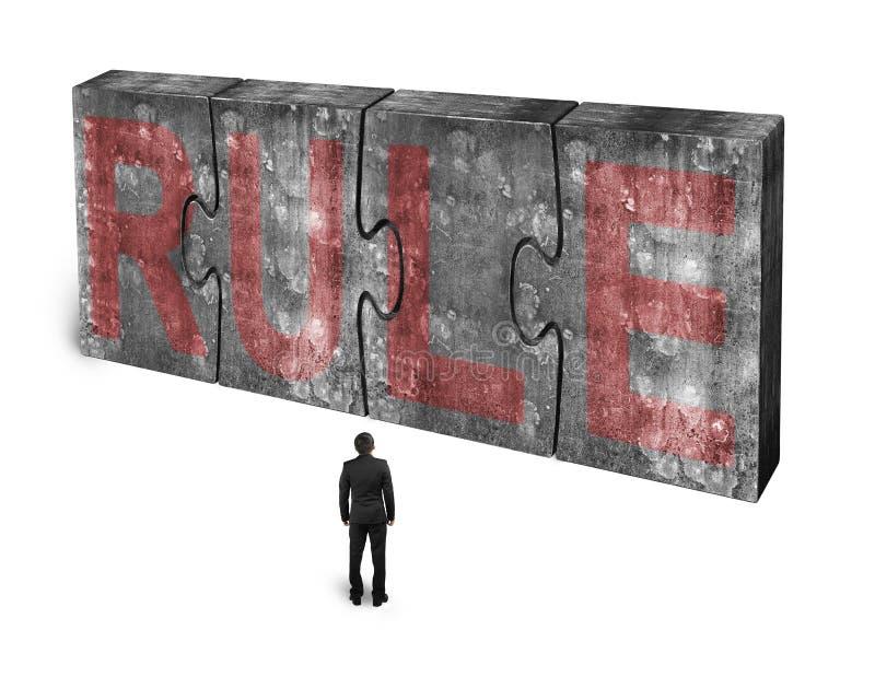 Mens die rood regelwoord op reusachtige concrete verbonden raadsels onder ogen zien stock afbeeldingen