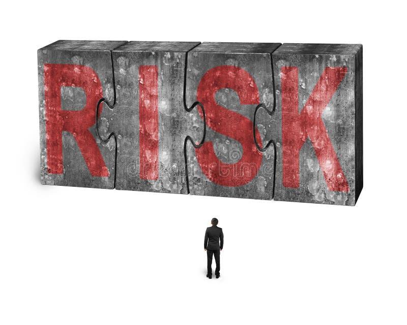 Mens die rood risicowoord op reusachtige concrete verbonden raadsels onder ogen zien royalty-vrije stock afbeeldingen
