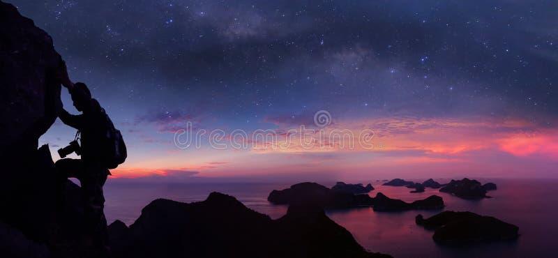 Mens die rots op de berg met panoramamening en miljoen sterrenmelkweg beklimmen stock foto's