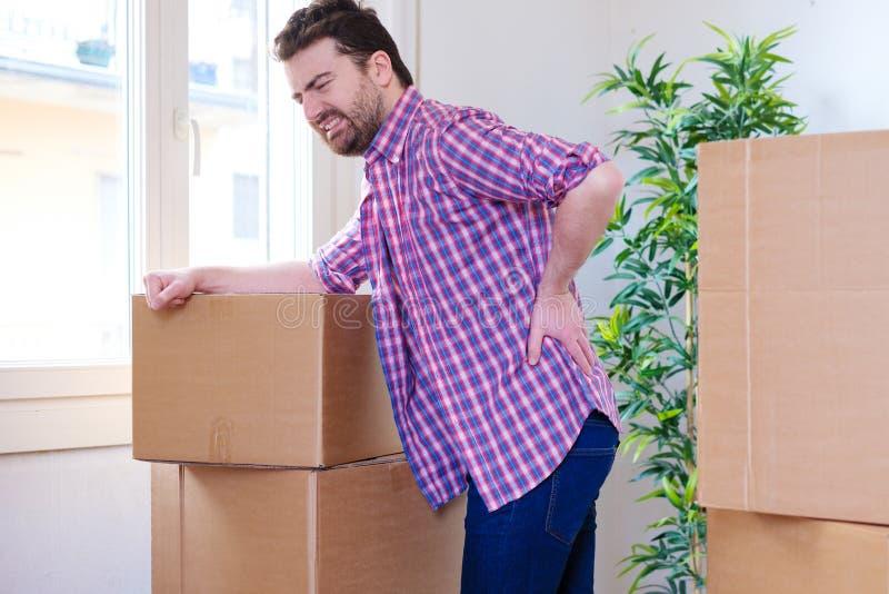 Mens die rugpijn gewrongen bewegende zware dozen voelen stock afbeeldingen