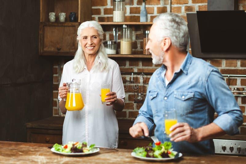 Mens die salade eten en zijn vrouw bekijken stock foto's