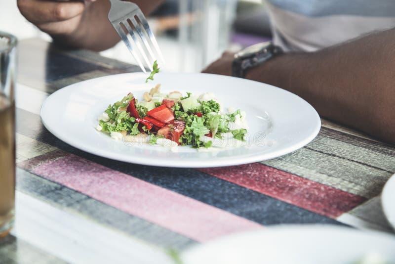 Mens die salade in koffie eten Bedrijfs lunch stock afbeeldingen