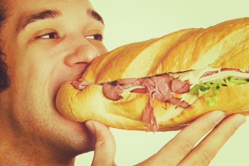 Mens die Sandwich eet stock fotografie