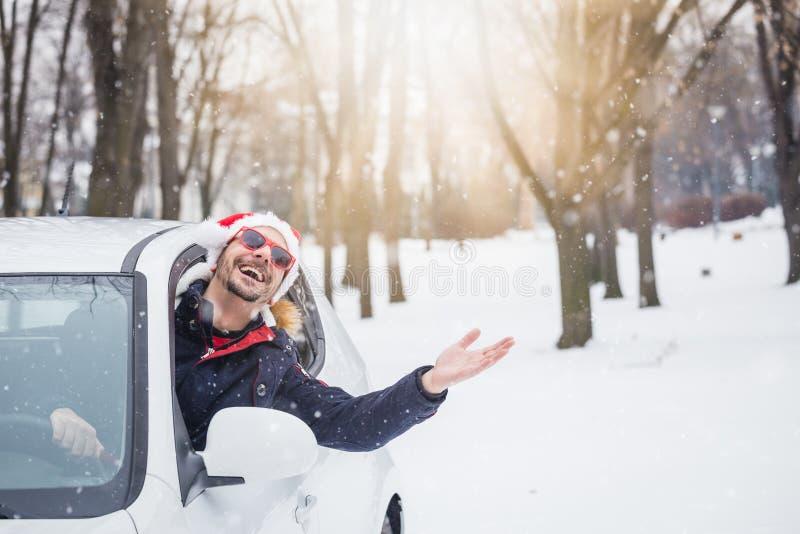 Mens die Santa Claus-hoed dragen en gelukkig omdat het sneeuwt royalty-vrije stock foto