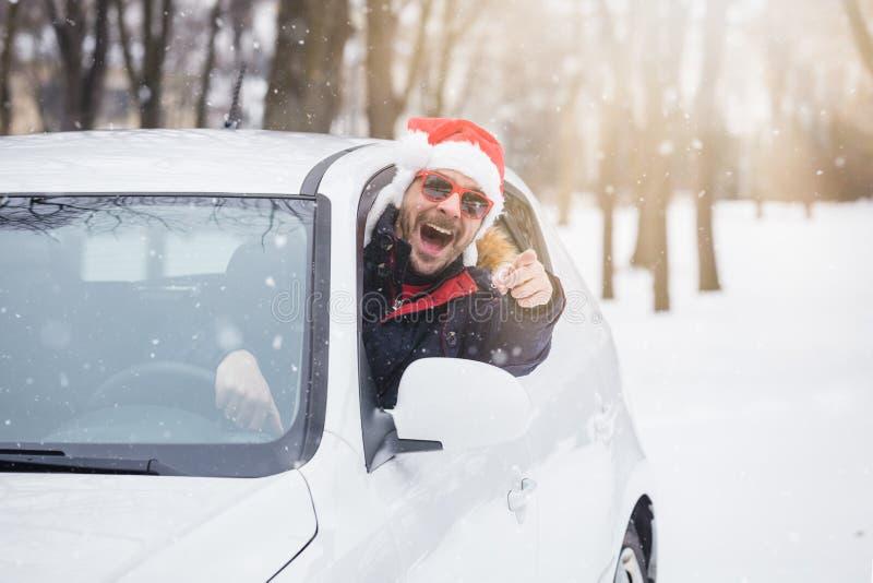 Mens die Santa Claus-hoed dragen en op autoraam leunen Het concept van de de winterreis stock afbeelding