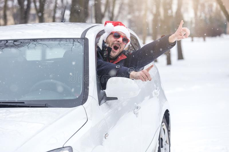 Mens die Santa Claus-hoed dragen en op autoraam leunen Het concept van de de winterreis stock foto's