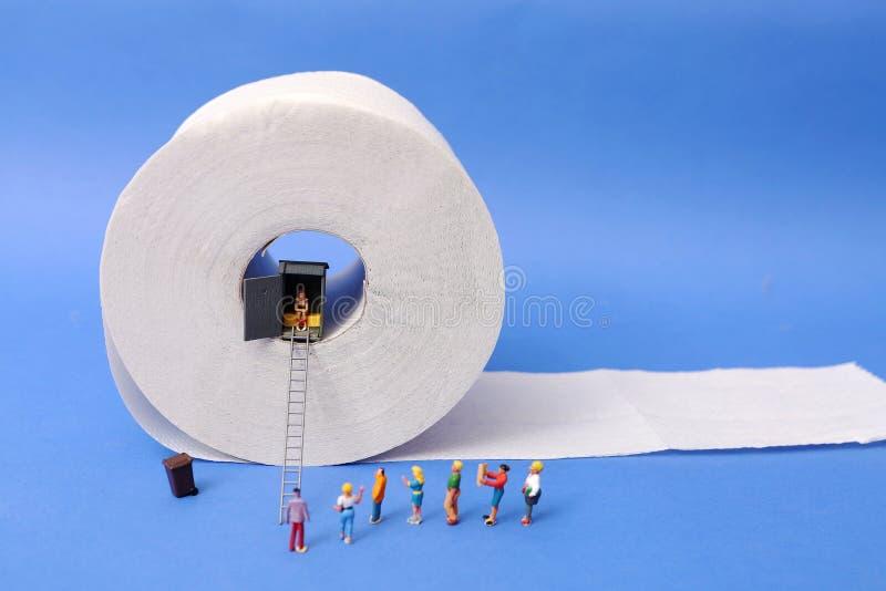 Mens die schaam- toilet, het reusachtige toiletpapier gewaagd rollen gebruiken, royalty-vrije stock foto